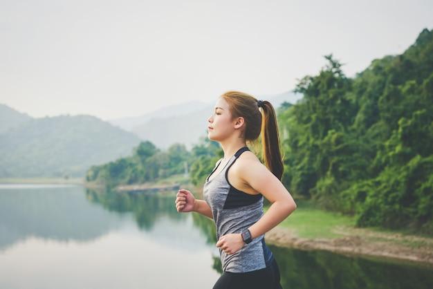 A mulher asiática nova que movimenta-se que corre no parque no ar fresco e veste o relógio dos esportes e que verifica seu desempenho.
