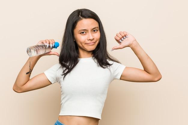 A mulher asiática nova que prende uma garrafa de água sente orgulhosa e auto-confiante, exemplo a seguir.