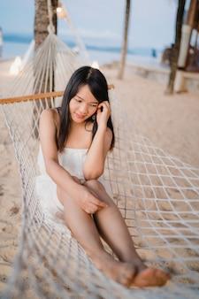 A mulher asiática nova que senta-se na rede relaxa na praia, feliz fêmea bonito relaxa perto do mar.