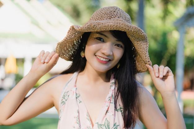 A mulher asiática nova que senta-se no banco relaxa na praia, feliz fêmea bonito relaxa perto do mar.
