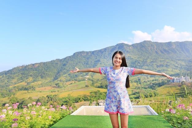 A mulher asiática nova que sente livre com os braços largos abre em árvores e nas montanhas bonitas.