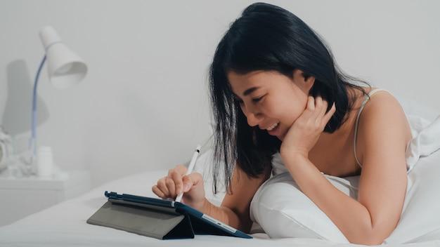 A mulher asiática nova que usa a tabuleta que verifica os meios sociais que sentem o sorriso feliz ao encontrar-se na cama após acorda na casa na manhã, o sorriso indiano atrativo da fêmea relaxa no quarto em casa.