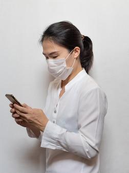A mulher asiática nova que veste a máscara cirúrgica impede usar o telefone móvel esperto isolado no branco, prevenção da manifestação do coronavírus de wuhan (covid-19) na área pública. cuidados de saúde e conceito médico.