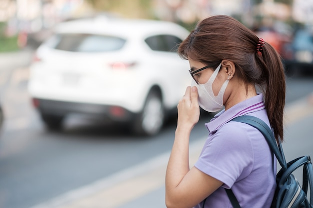 A mulher asiática nova que veste a máscara respiratória n95 protege e filtra pm2.5 (material particulado) contra a cidade de tráfego e poeira. conceito de saúde e poluição do ar