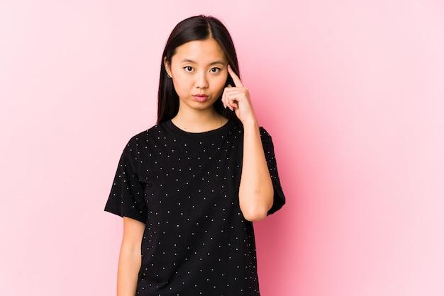 A mulher asiática nova que veste a roupa elegante isolou apontar o templo com o dedo, pensando, focalizado em uma tarefa.