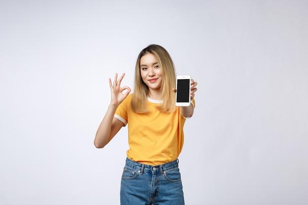 A mulher asiática nova que veste na camisa amarela está mostrando o sinal aprovado no fundo branco