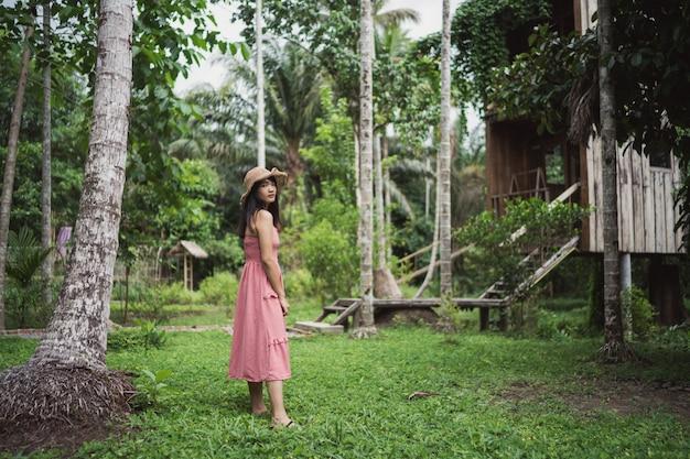 A mulher asiática nova relaxa na floresta, utilização feliz fêmea bonita relaxa o tempo na natureza.