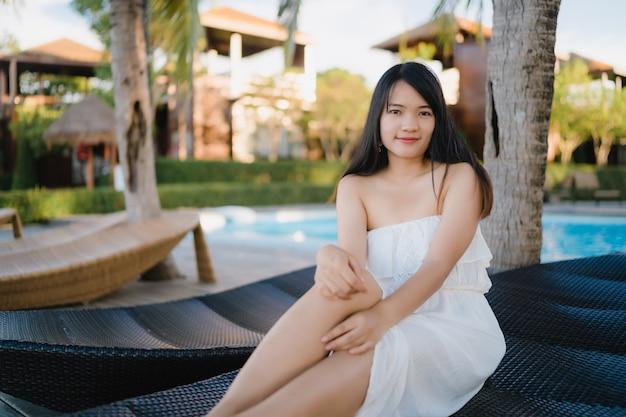 A mulher asiática nova relaxa perto da piscina no hotel, feliz fêmea bonito relaxa perto do mar.