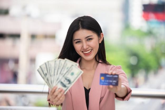 A mulher asiática nova veste o terno cor-de-rosa que mantém dólares contra o fundo borrado da cidade muito happ
