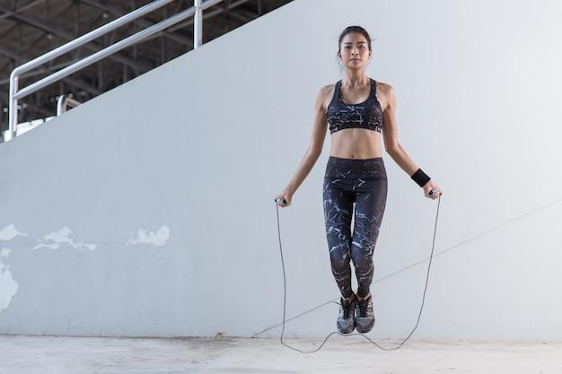 A mulher asiática ostenta a menina que faz exercícios com corda de salto.