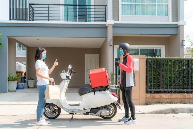 A mulher asiática pega o saco de comida de entrega da caixa e o polegar para cima sem contato ou entre em contato com o entregador com a bicicleta na frente da casa para distanciamento social por risco de infecção. conceito de coronavírus