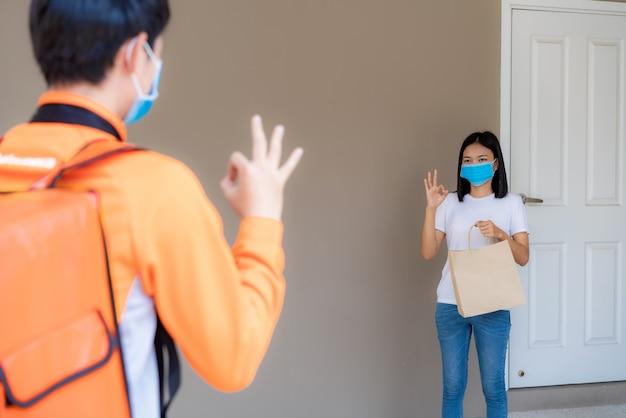 A mulher asiática pega o saco de comida de entrega da maçaneta da porta e o sinal de ok para contato sem contato ou livre de contato do condutor da entrega com bicicleta na frente da casa para distanciamento social por risco de infecção.