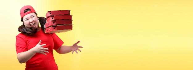 A mulher asiática pulou contente na tampa vermelha, dando pizza italiana de comida em caixas de papelão isoladas na parede amarela.