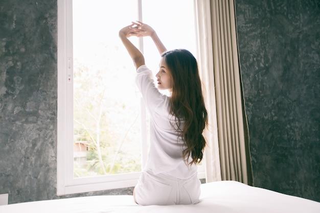 A mulher asiática que acorda em sua cama descansou inteiramente e abre as cortinas na manhã para obter o ar fresco.