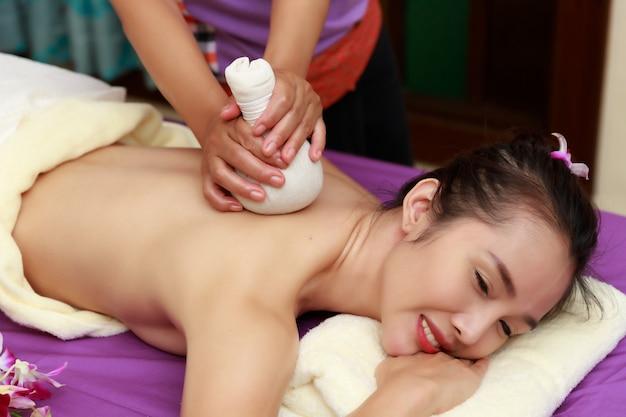A mulher asiática que aprecia um sal esfrega a massagem em termas.
