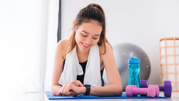 A mulher asiática que descansa e usa o smartwatch após o exercício em casa fundo.