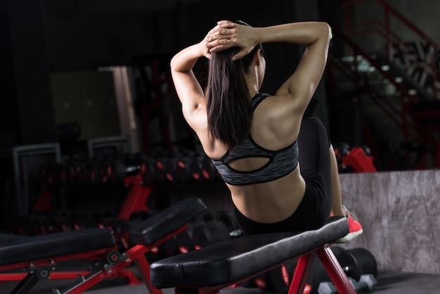 A mulher asiática que faz sentar-ups no gym, exercícios abdominais senta-se acima.