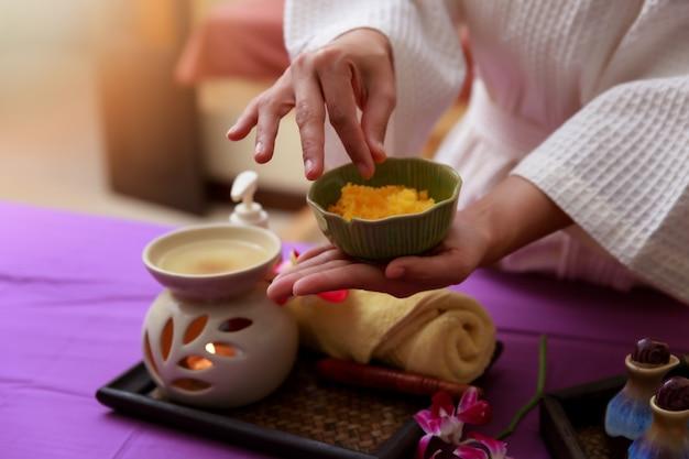A mulher asiática que guarda o sal esfrega para a massagem em termas.