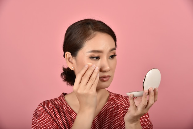 A mulher asiática que olha seu problema facial no espelho, sentimento fêmea irrita sobre sua aparência da reflexão mostra os sinais de envelhecimento da pele, problema de pele da tampa da composição.