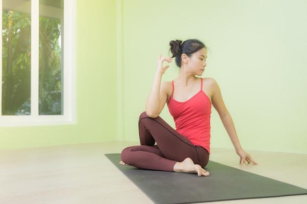 A mulher asiática que pratica no meio senhor dos peixes levanta, em um estúdio da ioga.