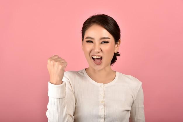 A mulher asiática que sente feliz e entusiasmada realiza sobre o sucesso no fundo cor-de-rosa, retrato da menina de sorriso do vencedor que comemora o uso para anunciar.