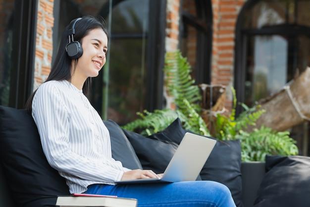 A mulher asiática que usa o computador portátil que trabalha, escutando a música com relaxa e feliz.