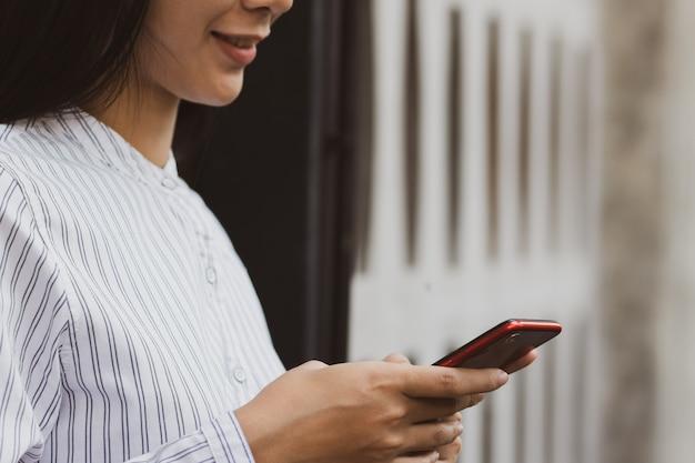 A mulher asiática que usa o funcionamento do smartphone, jogando no tempo livre com relaxa e feliz.