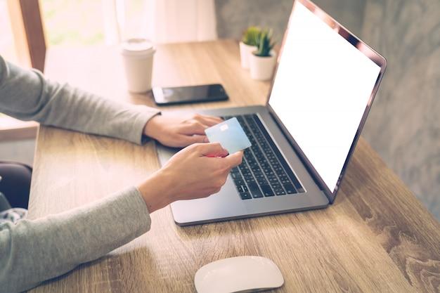 A mulher asiática que usa o laptop faz atividade on-line pagar cartão de crédito na tabela de madeira.