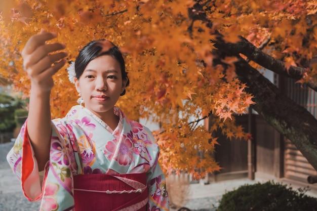 A mulher asiática que veste o quimono bonito que anda e viaja no jardim japonês dentro do templo com as folhas de bordo vermelhas no outono.