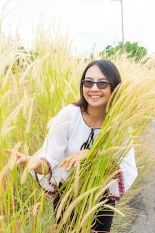A mulher asiática relaxa no campo de grama.