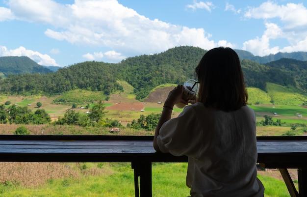 A mulher asiática senta e bebe o café.