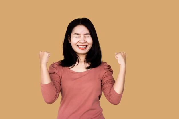 A mulher asiática sorri e comemora seu sucesso