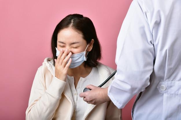 A mulher asiática tem alergia à garganta inflamada e tosse com máscara facial, espirros e tosse espalham a gota da doença de coronavírus, médico que rastreia o paciente infectado covid-19 no hospital.