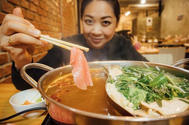 A mulher asiática tem o jantar do estilo do shabu para a estação do inverno.