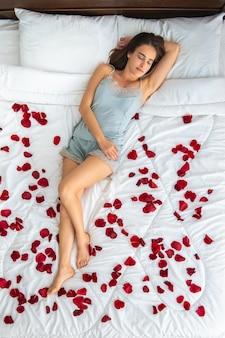 A mulher atraente dormindo na cama com pétalas de rosa. vista de cima