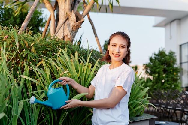 A mulher atraente regando flores, plantas em seu jardim.