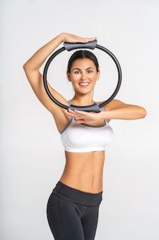 A mulher atrativa desportiva que faz pilates exercita para braços e ombros com anel.