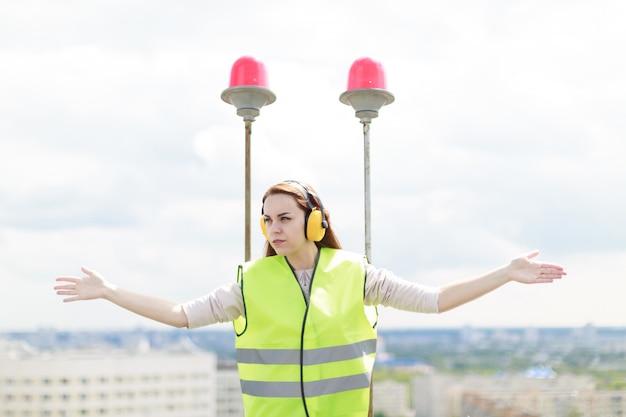 A mulher atrativa do trabalhador bonito no oeste verde e as capas protetoras para as orelhas estão no telhado, prenda a tabuleta
