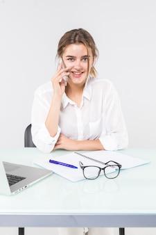 A mulher atrativa nova na roupa ocasional pastel que fala no telefone móvel, senta o trabalho na mesa com o portátil do pc isolado no fundo cinzento.