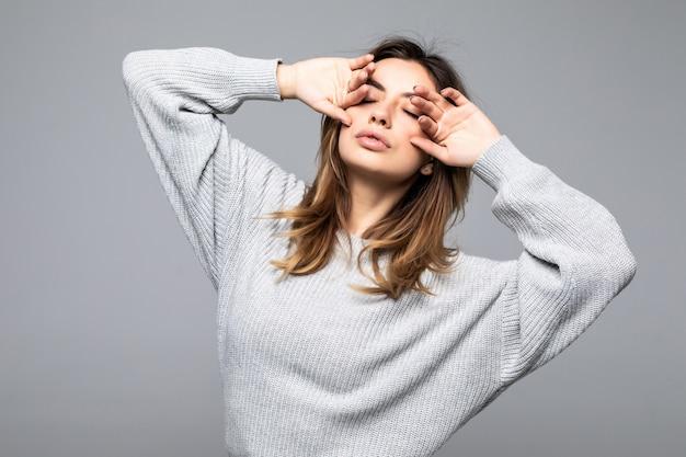A mulher atrativa positiva veste a camisola ocasional isolada contra a parede cinzenta