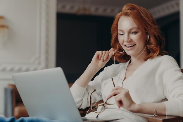 A mulher bem sucedida feliz feliz satisfeita tem a videoconferência, usa o computador portátil moderno