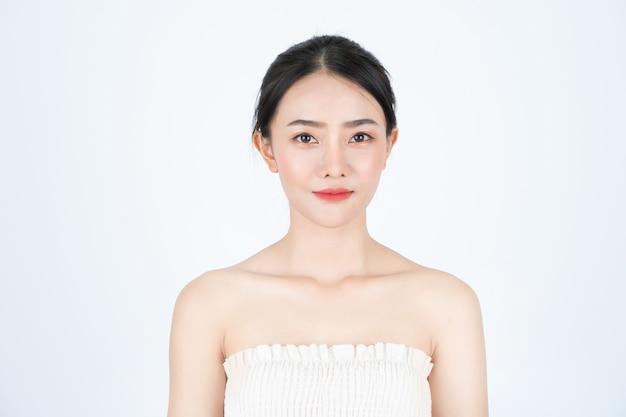 A mulher bonita asiática em camiseta branca, em posição frontal, tem uma pele saudável e brilhante.