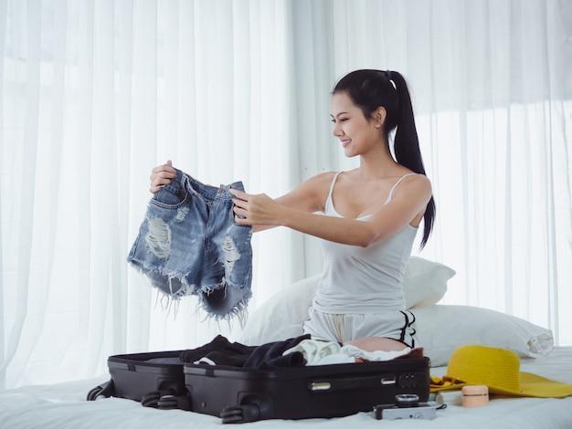 A mulher bonita asiática está preparando sacos para ir de férias
