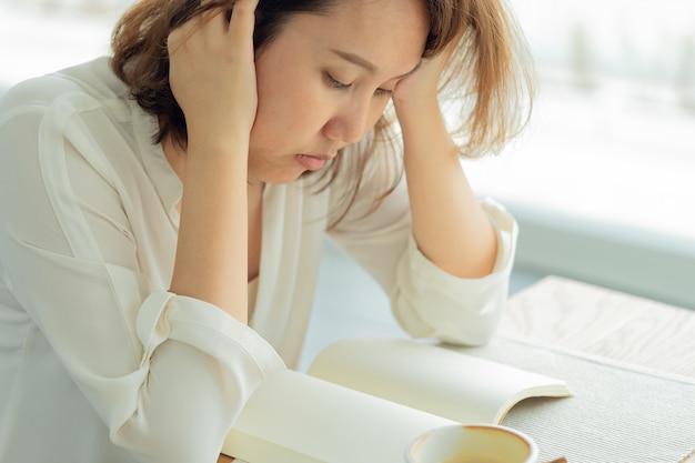 A mulher bonita asiática leu livros pela janela com esforço. use para se concentrar