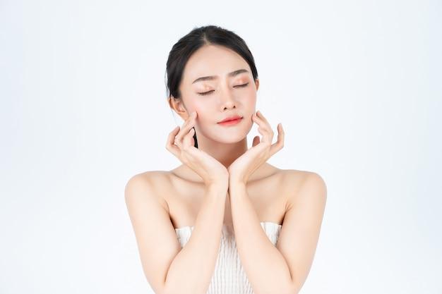 A mulher bonita asiática na camiseta branca mostra a pele brilhante e saudável.