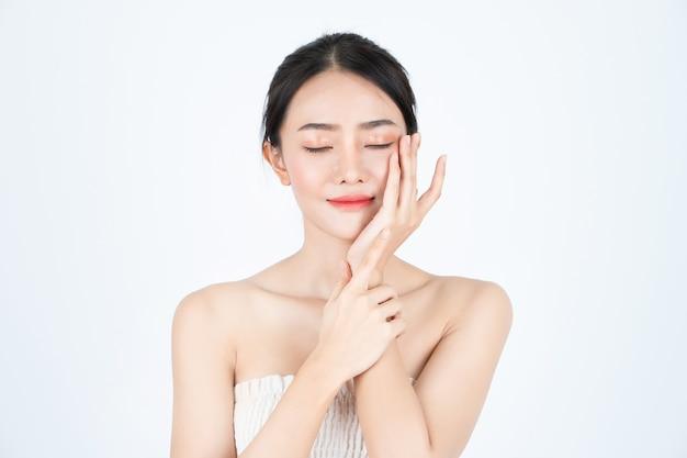 A mulher bonita asiática nova na camiseta branca, tem a pele saudável e brilhante.