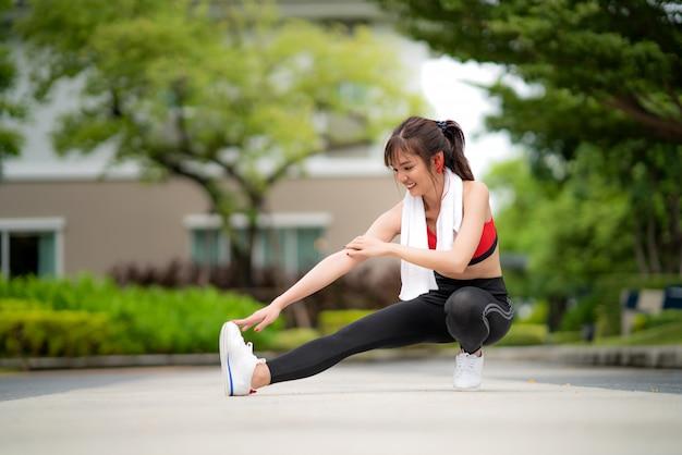A mulher bonita asiática que exercita o estiramento sozinho no parque público na vila, feliz e sorri na manhã durante a luz solar. etnia asiática do modelo da aptidão do esporte que treina o conceito exterior.