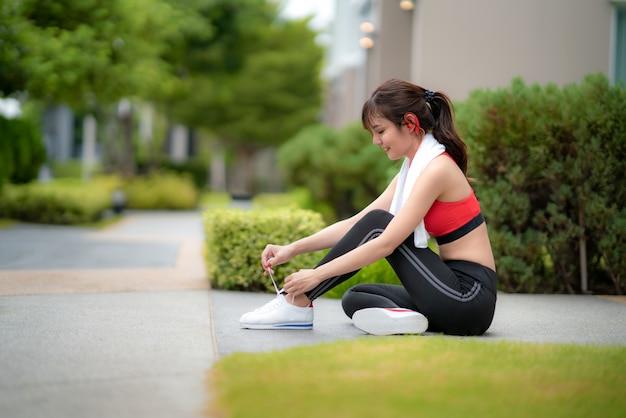 A mulher bonita asiática que senta-se para relaxa e que tenta laços na fonte de sua casa na vila, feliz e sorri na manhã durante a luz solar. etnia asiática do modelo da aptidão do esporte que treina o conceito exterior.