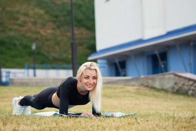 A mulher bonita da aptidão em um desgaste dos esportes que faz a prancha exercita fora. estilo de vida saudável esporte