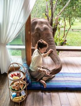 A mulher bonita de ásia senta na varanda de madeira e alimenta o elefante.